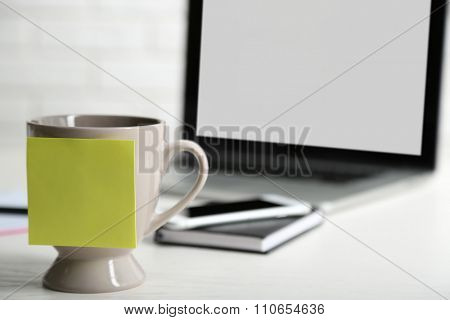Yellow adhesive note on coffee cup, on laptop background