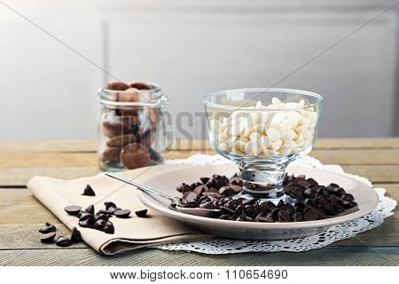 Chocolate morsels in glass jars on wooden background
