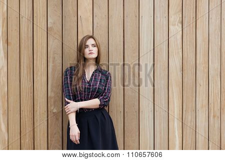 Young beautiful dreamy woman with good look posing for the camera against wooden wall