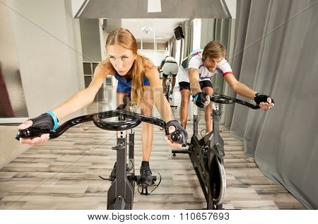 Young beautiful woman and a man working out determined in a modern cycling gym.