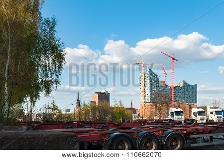 HAMBURG, GERMANY - May 1, 2013: Panorama view at the industrial port area.  Harbor cargo freight terminal German sea harbor with car park for trucks and famous Elbphilharmonic hall in background