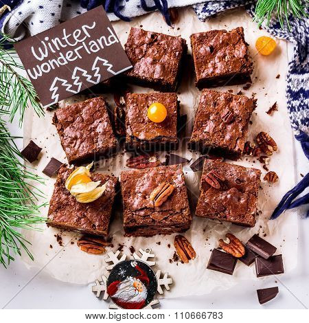 Brownie Pieces With Nuts And Christmas Card  On The White Paper.