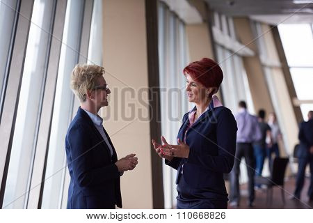 portrait  of two corporate business woman at modern bright office interior standing in group as team