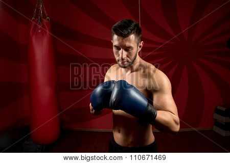 sportsman boxer with gloves and shirtless posing in gym