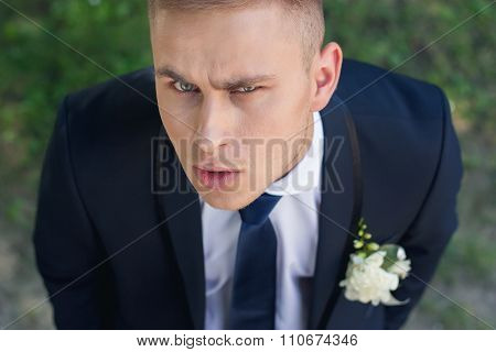 Frowning Groom Looks Into The Camera With Your Head