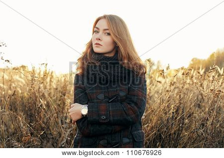 Noon portrait young thoughtful redhead woman in scarf and plaid jacket on faded meadow cold season