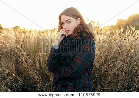 Noon portrait young thoughtful redhead woman in scarf plaid jacket on faded meadow cold season