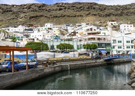 PUERTO DE MOGAN - NOVEMBER 27: Tourists enjoy the sunny weather and walking around the city on 27 November 2015 in Puerto de Mogan, Gran Canaria Island.