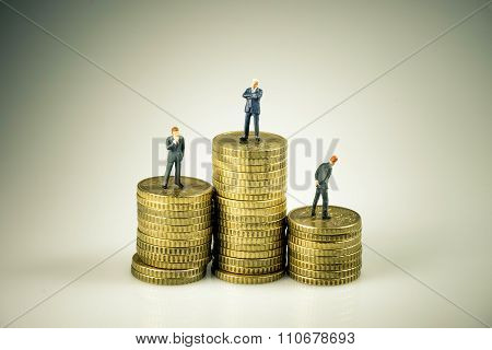 Business People On Pile Of Coins. Business Competition Concept