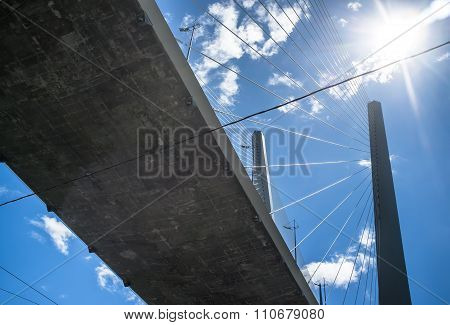 Cable-stayed Bridge From Below Against A Blue Sky With Clouds