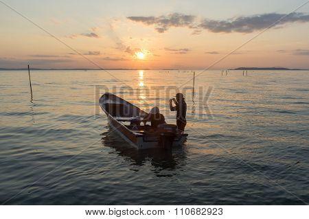 LABUAN FT, MALAYSIA - Oct 19, 2014.Fisherman in boat against sunrise over the Nagalang beach, Labuan