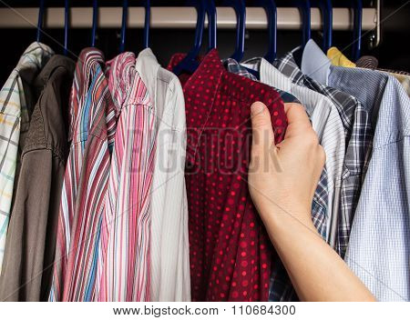 Person Chooses Shirt In The Closet