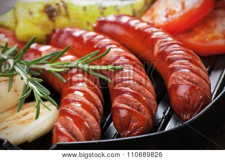 Grilled german sausages and vegetables in grilling pan