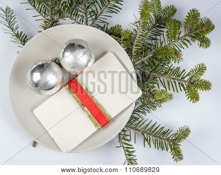 Traditional Christmas Eve white wafer on a plate with silver christmas balls
