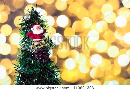 Santa Claus Doll Against Pine Nut With Ball And Christmas Tree On Yellow Bokeh Light Background