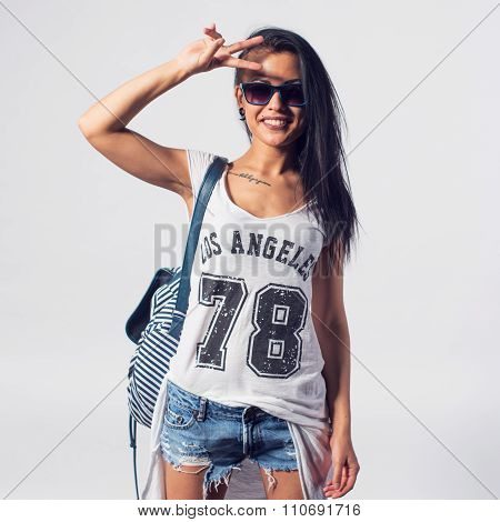 Young woman in sunglasses saluting showing v sign looking at camera. Portrait of trendy girl having