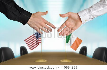 United States and Ireland diplomats shaking hands to agree deal