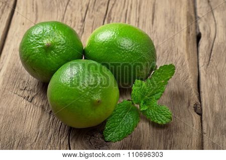 Fresh Limes With Mint Leaves On Wooden Surface