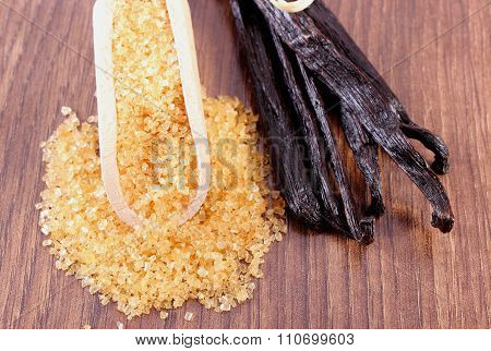 Sugar Cane On Spoon And Fragrant Vanilla Sticks On Wooden Surface Plank