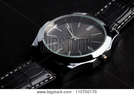 time, punctuality, object and accessory concept - close up of black classic male wristwatch