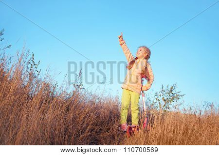 Little Girl In Bright Clothes With Scooter Shows A Finger To The Sky