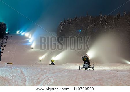 snow cannons working at night in the mountains