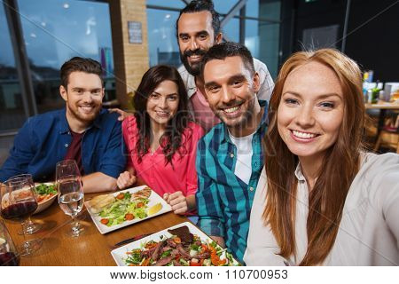 leisure, technology, friendship, people and holidays concept - happy friends having dinner and taking selfie by smartphone at restaurant