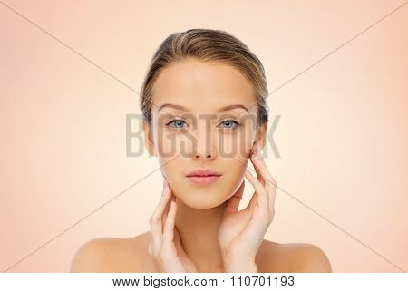 beauty, people and health concept - young woman with bare shoulders touching her face over beige background