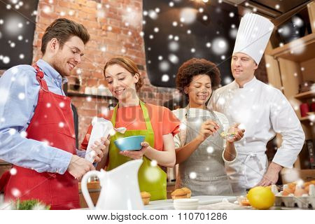 cooking class, culinary, bakery, food and people concept - happy group of friends and male chef cook baking in kitchen over snow effect