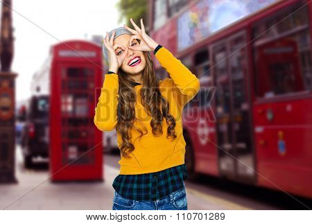people, travel, tourism and fashion concept - happy young woman or teen girl in casual clothes and hipster hat having fun over london city street background