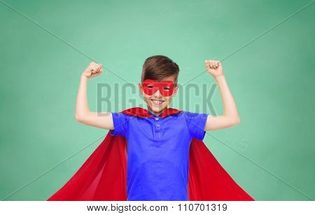 school, education, childhood, power and people concept - happy boy in red super hero cape and mask showing fists over green chalk board background