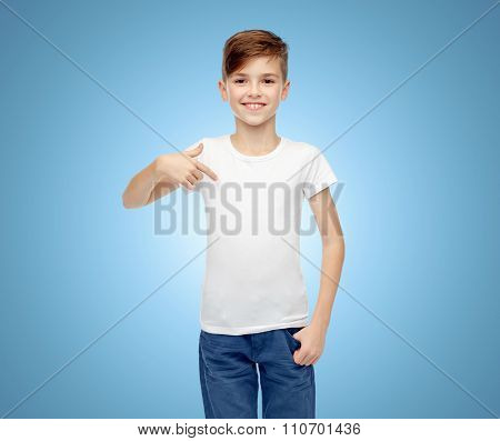 childhood, fashion, advertisement and people concept - happy boy in white t-shirt and jeans pointing finger to himself over blue background