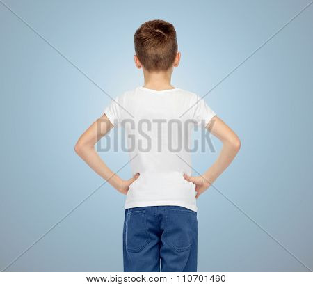 childhood, fashion, advertisement and people concept - boy in white t-shirt and jeans over blue background from back
