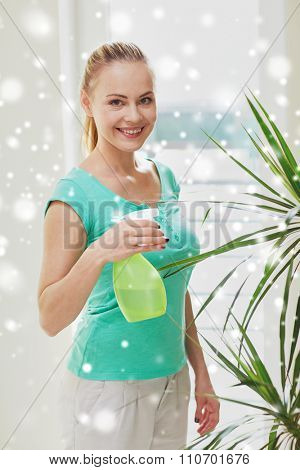 people, housework and care concept - happy woman with spray bottle spraying houseplants at home over snow effect