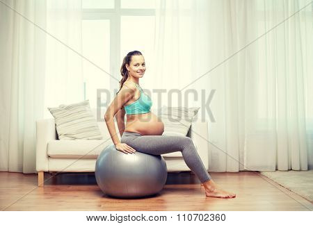 pregnancy, sport, fitness, people and healthy lifestyle concept - happy pregnant woman exercising on fitball at home