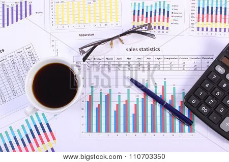 Pen, Glasses, Calculator And Cup Of Coffee On Financial Graph, Business Concept