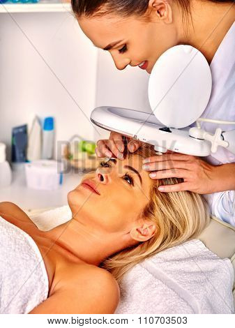 Woman middle-aged lying in spa salon with cosmetic lamp eyebrow correction  .