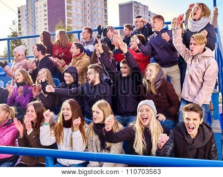 Sport fans hands up clapping and singing on tribunes. Group people.