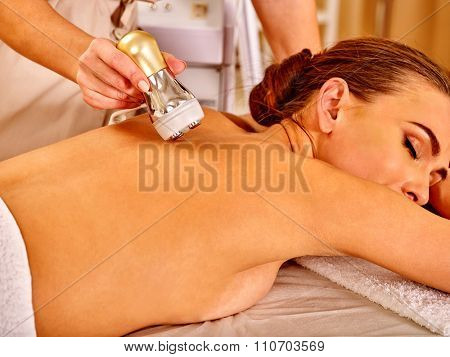 Lying woman with close eyes receiving electroporation back therapy at beauty salon.