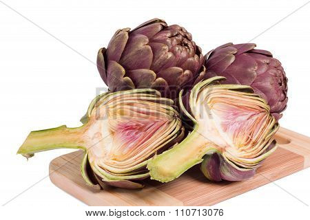 Fresh Artichokes On A Cutting Board