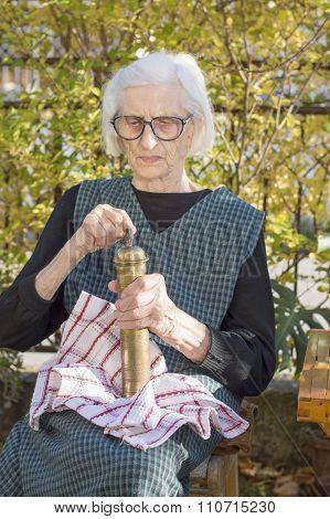 Grandma Grinding Coffee On A Vintage Coffee Grinder