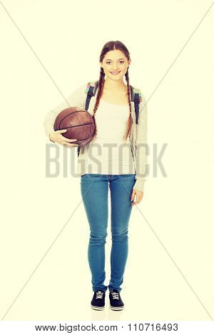 Teenager with schoolbag and basket ball.