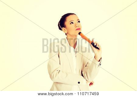 African thoughtful businesswoman with big pen.
