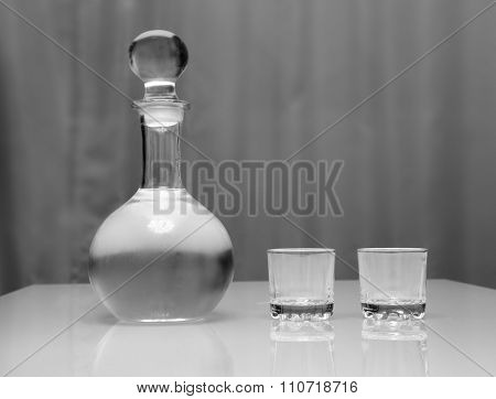 cold decanter and two glasses with vodka standing on a glass table