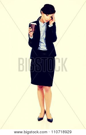 Exhausted businesswoman holding a cup of coffee.