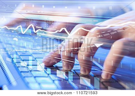 Hands using white keybord and digital graphs on screen