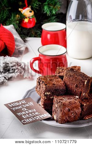 Brownie Pieces With Nuts On The Plate, Two Cups Of Milk And Bottle. Christmas Tree.