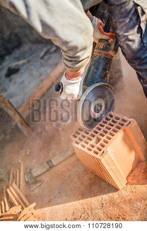 Male Worker Cutting Bricks With Angle Grinder Power Tool, Dust And Debris On Construction Site