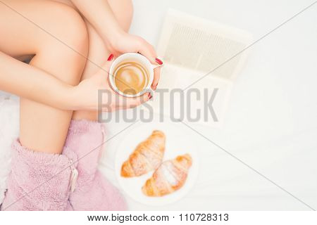 Close-up Of Woman Legs With Fluffy Slippers Drinking A Coffee And Reading A Good Book