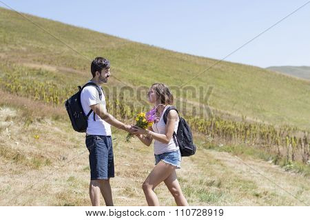 Hiker Gives Flowers To A Woman On A Hiking Trip